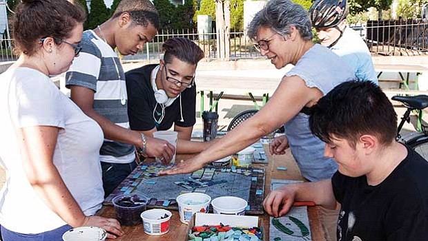 Community members place tiles on a mosaic.