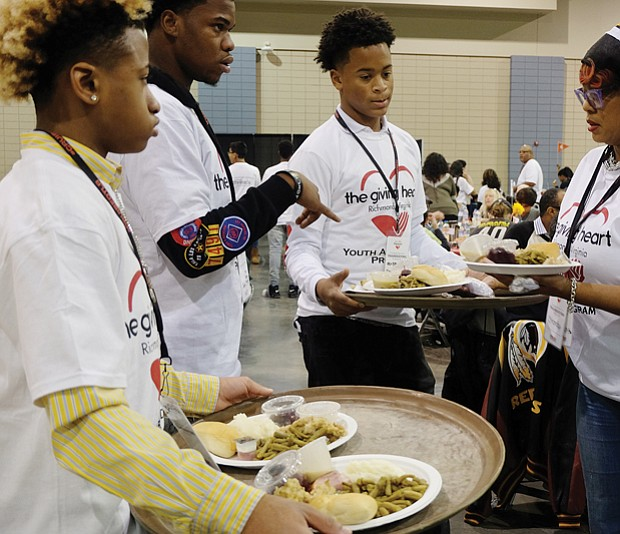 Holiday sharing // Volunteers Malik Childs, left, Sidney Evans, Davon Courtney and Shonda Harris-Muhammed prepare to serve meals at the Giving Heart Community Thanksgiving Feast at the Greater Richmond Convention Center.
