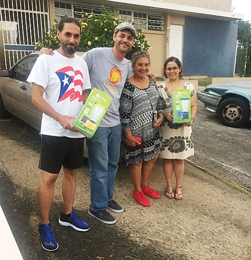Roxbury native David Ortiz (2nd from left) has distributed 6,000 solar lanterns to Puerto Rican families lacking power.
