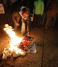 Palestinian burn a poster of the U.S. President Donald Trump during a protest in Bethlehem, West Bank, Wednesday, Dec. 6, 2017. Defying dire, worldwide warnings, President Donald Trump on Wednesday broke with decades of U.S. and international policy by recognizing Jerusalem as Israel's capital. (AP Photo/Nasser Shiyoukhi)