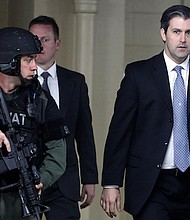 In this Monday, Dec. 5, 2016, file photo, former South Carolina officer, Michael Slager, right, walks from the Charleston County Courthouse under the protection of the Charleston County Sheriff's Department after a mistrial was declared for his trial in Charleston, S.C. Slager fatally shot a black motorist, Walter Scott, in 2015. (AP Photo/Mic Smith, File)