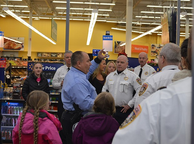 Officer Frank Coleman addresses volunteers before the start of the Santa Cops shopping spree at Walmart in Joliet.