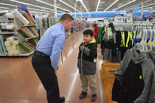 Jacob, 7, along with Officer Phil Miller check the fit on a new jacket he picked out during the Santa Cops shopping event at Walmart in Joliet.
