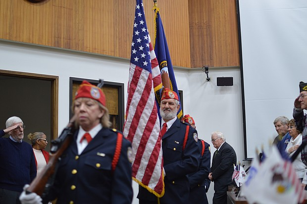 Jack Picciolo (background) salutes as the Abraham Lincoln Cemetery color guard posts the flag before a ceremony honoring his volunteerism on behalf of vets this week.