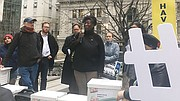 Labor activists from across the state convened in front of Secretary of State William Galvin's Elections Division Office at One Ashburton Place office to celebrate the submission of signatures for two ballot questions: One that would raise the Massachusetts minimum wage to $15 an hour by 2022 and another that would mandate paid sick time for Massachusetts workers.