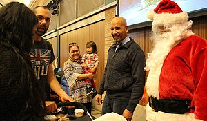 Bronx Borough President Ruben Diaz Jr. assists Santa Claus, as part of the Wildlife Conservation Society's Bronx Zoo Toy Giveaway for the children of Veterans and Active Military Members event.