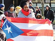 A marcher holds the Puerto Rican flag.