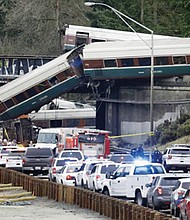 On its first ever run along a faster new route, an Amtrak Cascades train bound for Portland derailed on a curve and plunged off an overpass onto I-5 south of Seattle Monday, killing three people and injuring more than 70 others. (AP photo)