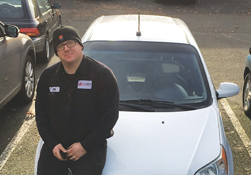 Lead auto mechanic J.R. Watkins of Elite OnSite and the car he fixed up for a donation to a local family in need.
