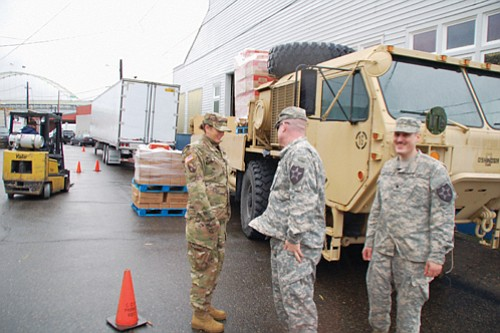 Members of the Active and Reserve National Guard and American Military Encouragement Network volunteer to distribute holiday food donations from ...