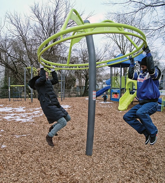 "Monica and Barry Gamble, try out a ring swing on the new ""Tot Lot"" last Friday at the city's newest playground for children. Location: 2001 3rd Ave. in North Side's Highland Park. The city Department of Parks, Recreation and Community Facilities developed the playground."