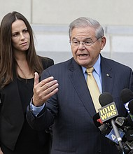 In this Sept. 6, 2017 photo, while his daughter Alicia Menendez looks on, Sen. Bob Menendez talk to reporters as he arrives to court for his federal corruption trial in Newark, N.J. (AP Photo/Seth Wenig, File)