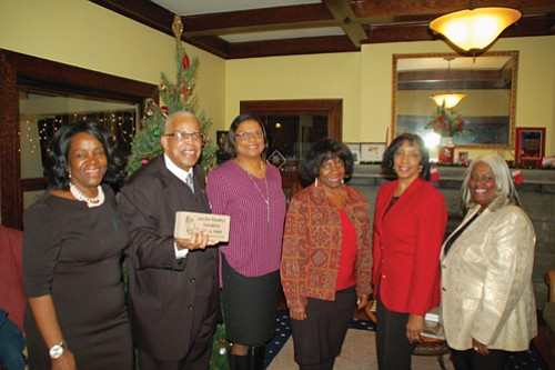 A holiday social to help the historic Allen Temple CME church raise donations to rebuild after a 2015 fire draws members of the church's Honorary Capital Campaign.  Rev. LeRoy Haynes (second from left) shows one of the legacy bricks that are being sold to raise additional contributions.