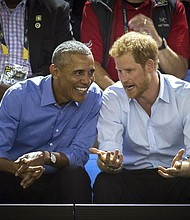In this Friday, Sept. 29, 2017 photo, former U.S. President Barack Obama, center left, and Britain's Prince Harry watch wheelchair basketball at the Invictus Games in Toronto. Obama told Prince Harry in an interview broadcast Wednesday, Dec. 27, 2017 that he felt serene the day he left the White House despite the sense that much important work remained unfinished. (Chris Donovan/The Canadian Press via AP, File)