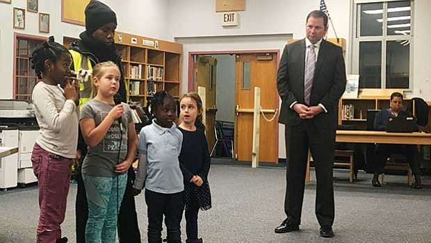 Crystal Lockett, school traffic supervisor, with students from the Winship Elementary School, offering testimony at a community meeting while John Hanlon, BPS Chief of Operations, looks on.