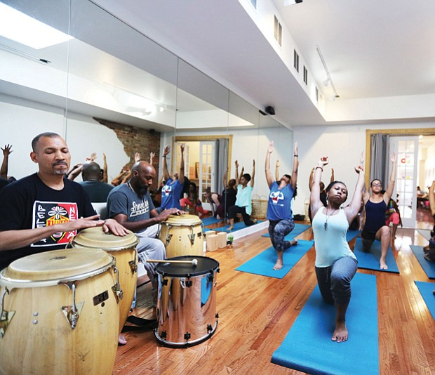 Ram Bhagat, left, and his drum circle set the beat for a yoga session in June at a Jackson Ward juice and yoga bar.