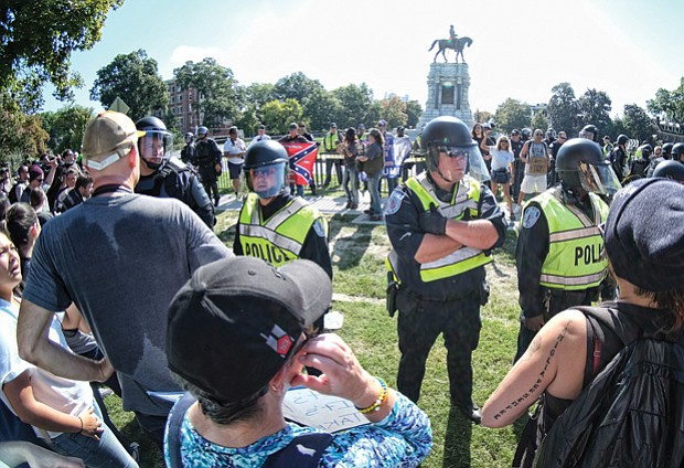 Richmond Police officers in riot gear separate neo-Confederates and counterprotesters during a rally Sept. 16 at the Robert E. Lee monument in Richmond.