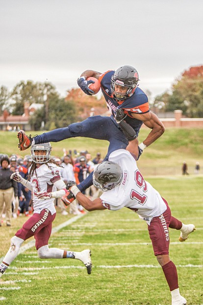 "Virginia State University tailback Trenton ""Boom"" Cannon goes airborne for a touchdown in the Trojans' nail-biting 40-39 victory over Virginia Union University on Nov. 4."