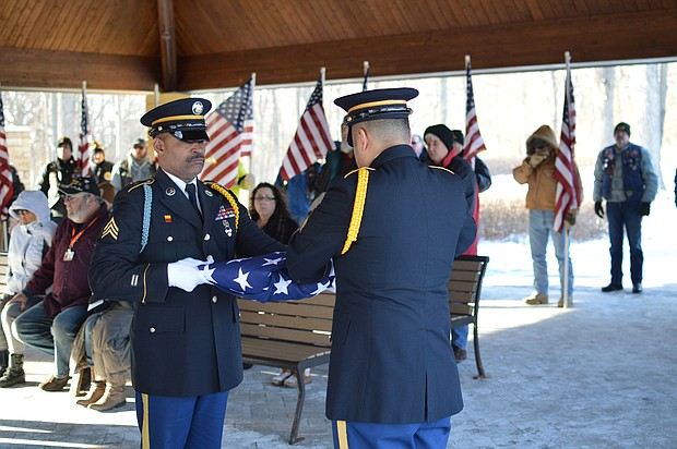 Volunteers fold the flag to present to those who served as the surrogate families for homeless veterans Wallace Boyd and Melvin Harris at a ceremony at Abraham Lincoln Cemetery in Elwood.