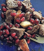 Pomegranate seeds stir fried with meat, onions and garlic.