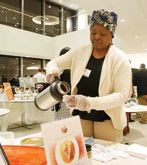 Paulette Ngachoko pours samples of her Cameroonian peanut sauce at a Food Biz 101 pitch event.