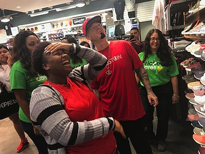 "YES Prep senior Davenese Bailey shares her excitement with Houston rapper Paul Wall while shopping for shoes at The Galleria. Cricket Wireless marketing manager Susan Cochran (right) joins them. Cricket Wireless was the sponsor of the ""surprise"" holiday shopping spree for the students."