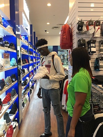 YES Prep junior Jason Akpabio shops for shoes at The Galleria, the surprise recipient of a $1000 holiday shopping spree from Cricket Wireless.