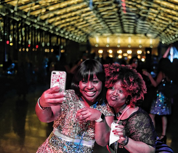 "Later Sunday night, the 18-and-older crowd turned out for ""Le Masque 007 NYE Celebration"" at the Main Street Station train shed. About 250 people attended the party that had a James Bond Casino Royale theme.  Malekah Mason, left, and Myaira Mason, ring in 2018 with champagne and a selfie at the event."