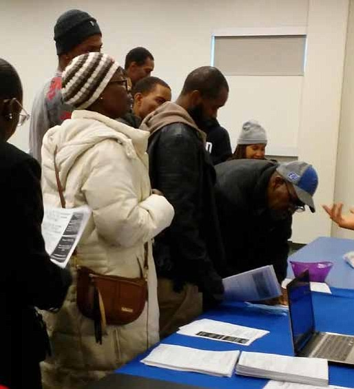 Job seekers stand in line to wait their turn to receive information about available jobs.