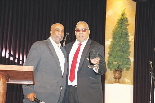Portland Observer Publisher Mark Washington receives an award of appreciation from Pastor C.T. Wells of Emmanuel Temple Church during a Dec. 31 ceremony.