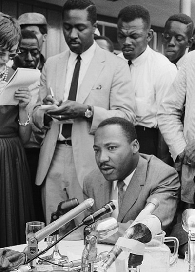 Clarence B. Jones who was part of Martin Luther King's legal team, takes notes behind Dr. King at a press conference in Birmingham, Alabama in February 1963.