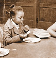 Children at a free breakfast program in 1969 sponsored by the Portland Black Panthers at the Highland Community Church of Christ. Organizer Kent Ford sits with the children.