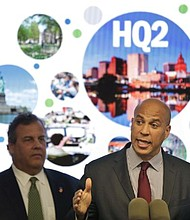 In this Monday, Oct. 16, 2017, file photo, New Jersey Sen. Cory Booker, right, speaks while New Jersey Gov. Chris Christie stands behind him during an announcement in Newark, N.J. New Jersey lawmakers have signed off on $5 billion in tax breaks to Amazon in an effort to convince the company that Newark would be the best location for the company's planned second headquarters. (AP Photo/Seth Wenig, File)