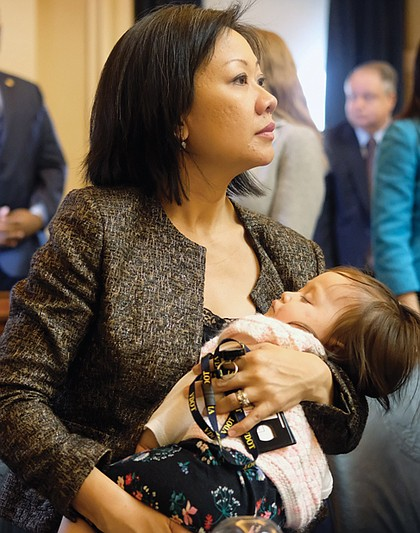 Fairfax Delegate Kathy Tran takes in the action on her first day as a legislator while her less than impressed baby, Elsie, naps.