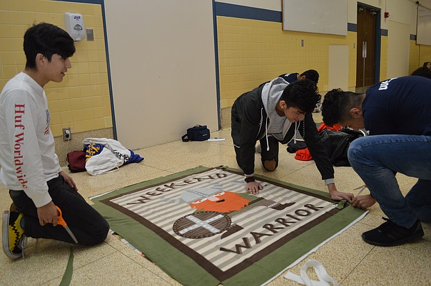 Seniors Edwin Zamudio, Nick Rios and Armando Angeles assemble a blanket on the floor of the gym at Joliet Central High School during the MLK Day of Service event on Monday.