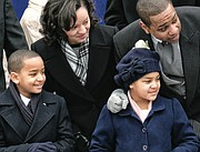 Lt. Gov. Justin e. Fairfax and his wife, Dr. Cerina Fairfax, enjoy the performers and units in the inaugural parade from the stands with their children, Cameron, left, and Carys.