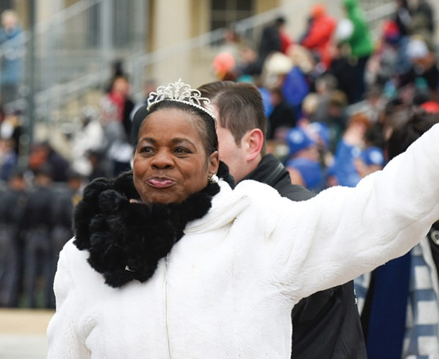 Deborah Pratt of the Eastern Shore, who holds the title of Virginia's fastest oyster shucker, waves to the crowd during the parade.