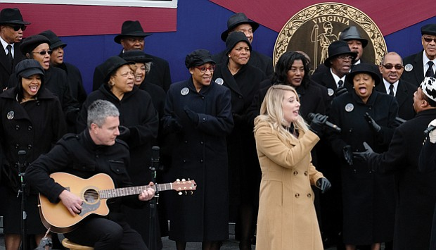 Larry Bland and the Volunteer Choir accompany the mother-daughter country group, Marna & Macy, in the final song at the inaugural ceremony. They are, from right, Marna Bales; her daughter, Macy Kaczmarek, center; and Ms. Bales' husband, Jody Boyd, on acoustic guitar.