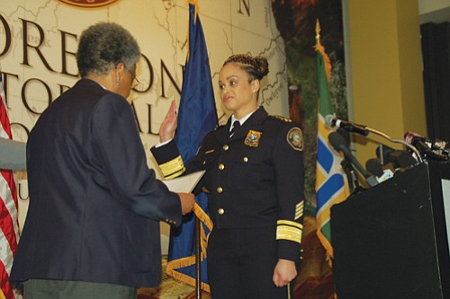 With the Oregon Historical Society's new exhibit 'Racing for Change, Oregon's Civil Rights Years' as a backdrop, Portland Police Chief Danielle Outlaw (right) takes the oath of office Monday from retired Portland Police Officer Carmen Sylvester, the first African American female officer to be hired by the city in 1973.