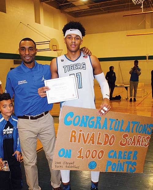 Rivaldo Soares is presented a banner congratulating him on reaching 1,000 points Jan. 24 at the O'Bryant School of Mathematics and Science from headcoach Drew Brock. A junior on the boys varsity basketball team at the school, he has excelled in the sport and hopes to help lead the Tigers to a successful run in the upcoming BPS city league championship in mid February and the state tournament in March.