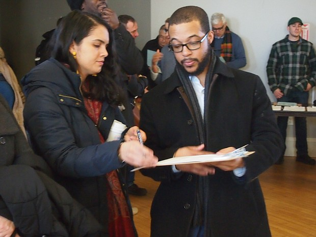 Claudia Baez signs nomination papers for 14 Suffolk candidate Segun Idowu.