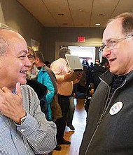 Political activist Tony Barros speaks with U.S. Rep. Michael Capuano during the Ward 18 Democratic Caucus at the municipal building in Hyde Park.