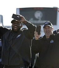 Philadelphia Eagles defensive tackle Fletcher Cox, left, and head coach Doug Pederson approach a fence where fans gathered to welcome the team Monday, Feb. 5, 2018, at Philadelphia International Airport a day after defeating the New England Patriots in Super Bowl 52. (AP Photo/Julio Cortez)