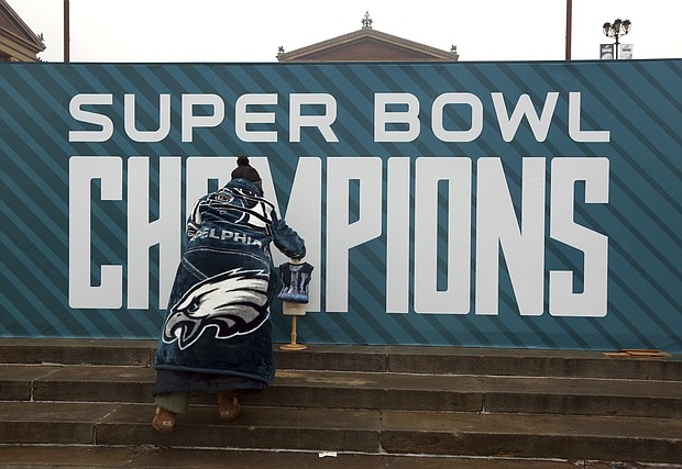 Philadelphia Eagles fan and fashion designer Nancy Volpe Beringer places a small dressmaker's form with an outfit she says she made and would like to give Eagles' Nick Foles daughter, Lily, on the steps of the Philadelphia Museum of Art, Wednesday Feb. 7, 2018, in Philadelphia. (AP Photo/Jacqueline Larma)
