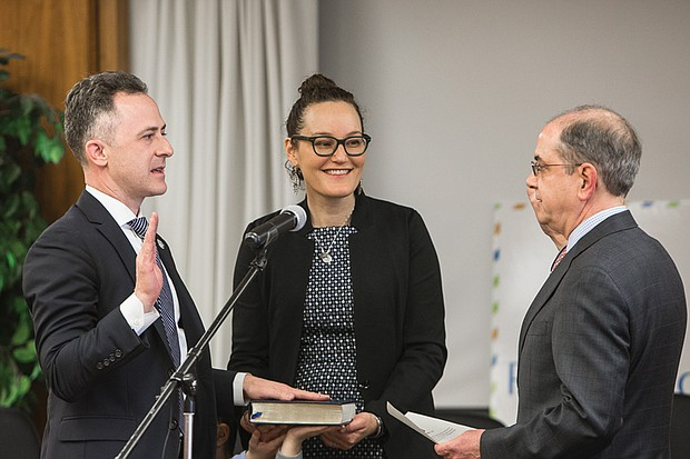 Jason Kamras, left, is sworn in as Richmond's new schools superintendent as his wife, Miwa, holds his late grandfather's Torah. Performing the ceremony on Feb. 1 is Edward F. Jewett, clerk of the Richmond Circuit Court.