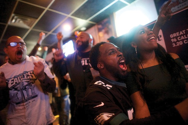 Philadelphia Eagles fans Devon Bailey, left, and Emma Dickson cheer on their team Sunday at Reales Bar in Philadelphia.