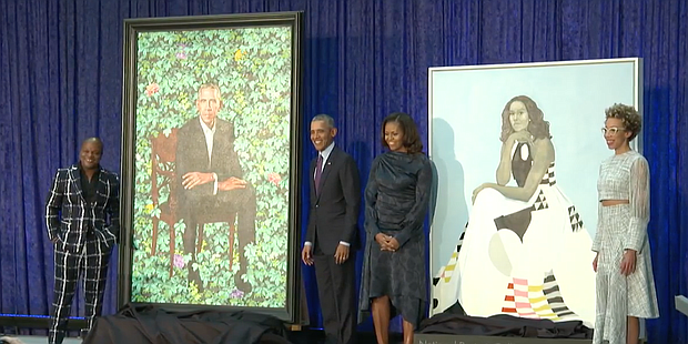 President Barack Obama and First Lady Michelle Obama stand with their official portraits.