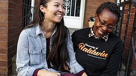 """In this Nov. 11, 2017, photo, provided by Reveal, Rachelle Faroul, right, and her partner, Hanako Franz, sit outside their new home in Philadelphia. """"I had a fair amount of savings and still had so much trouble just left and right,"""" said Faroul, who was rejected twice by lenders when she tried to buy a brick row house close to Malcolm X Park in Philadelphia. (Sarah Blesener/Reveal via AP)"""