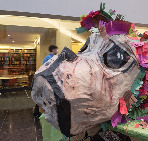 A giant papier-mâché dog's head sits on a workbench, a symbol of the year that is to usher in a time of fairness and equality.