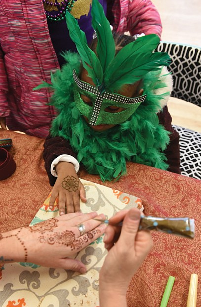 After donning a mask and feather boa, 4-year-old Marshall Howard gets a henna tattoo during the main event inside the center on West 15th Street. Music, performances by several groups and Cajun-style food were featured, along with a King Cake.